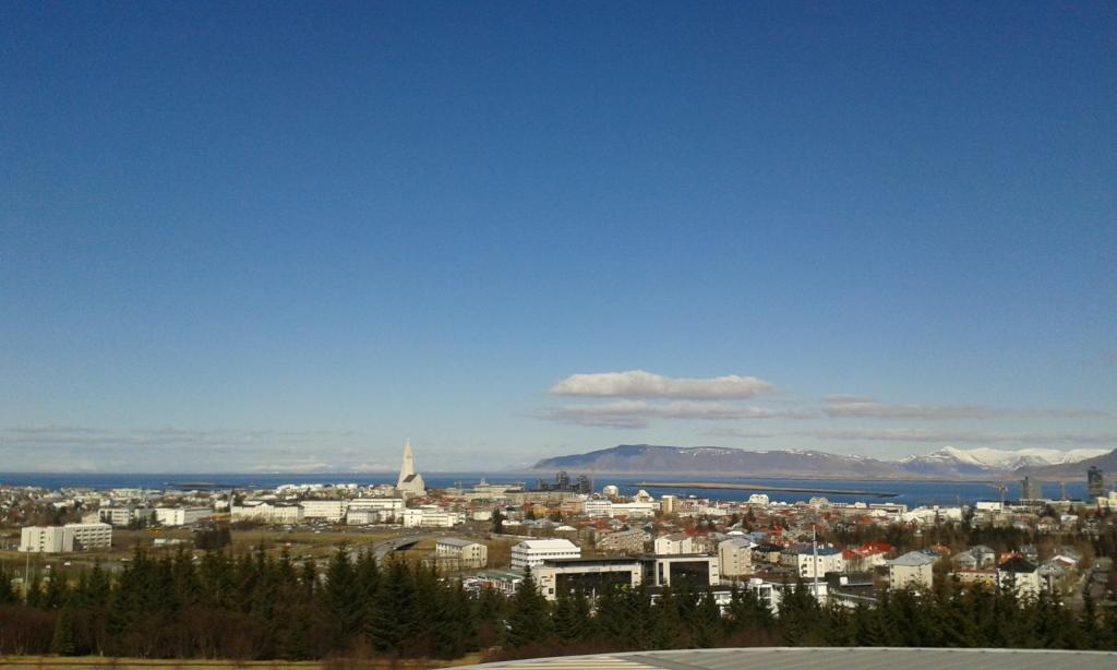Panorama Reykjavik-ului, dominată de Hallgrimskirkja, văzută de pe terasa de la Perlan, și brazii de pe colina Öskjuhlíð